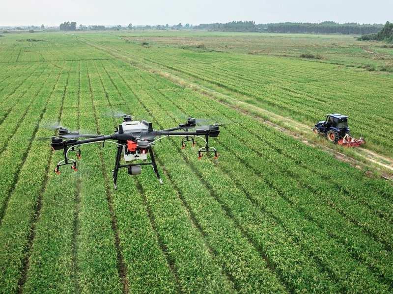 トラクターと並走する農業用ドローンの写真