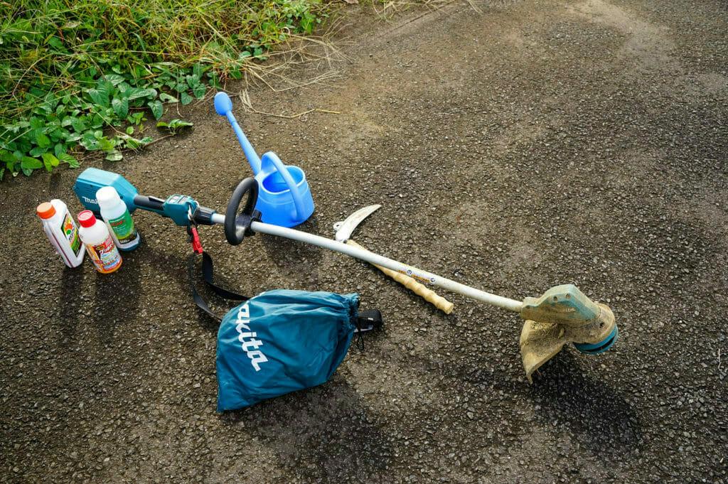 電動刈り払い機と鎌(カマ)、除草剤、ジョウロと除草道具一式