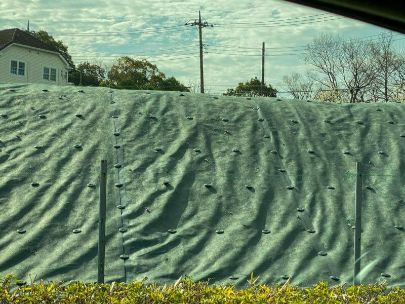 斜面に貼られている大規模な防草シート
